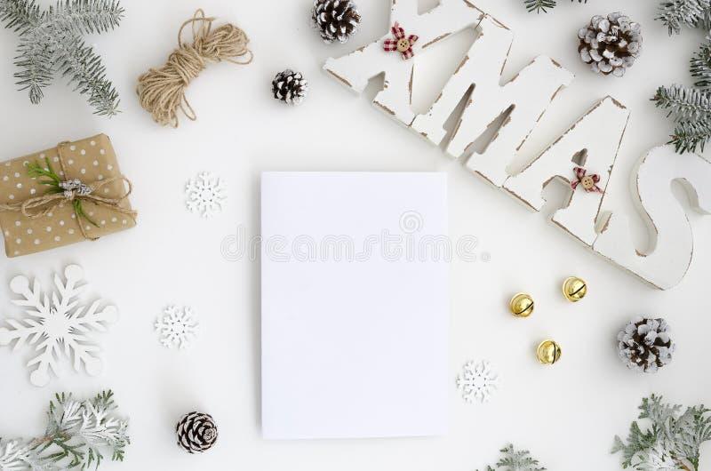Sikten för kortet för modelljulhälsningen lägger den bästa och xmas-träbokstäver, framlänges på en vit bakgrund med gåvaasken, sö royaltyfri fotografi