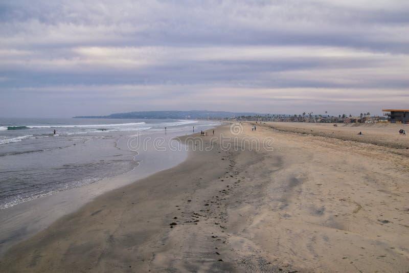 Sikten från beskickningstranden i San Diego, av pir, brygga och sand, runt om surfare, inklusive varnande tecken, palmträd, vågor royaltyfria foton