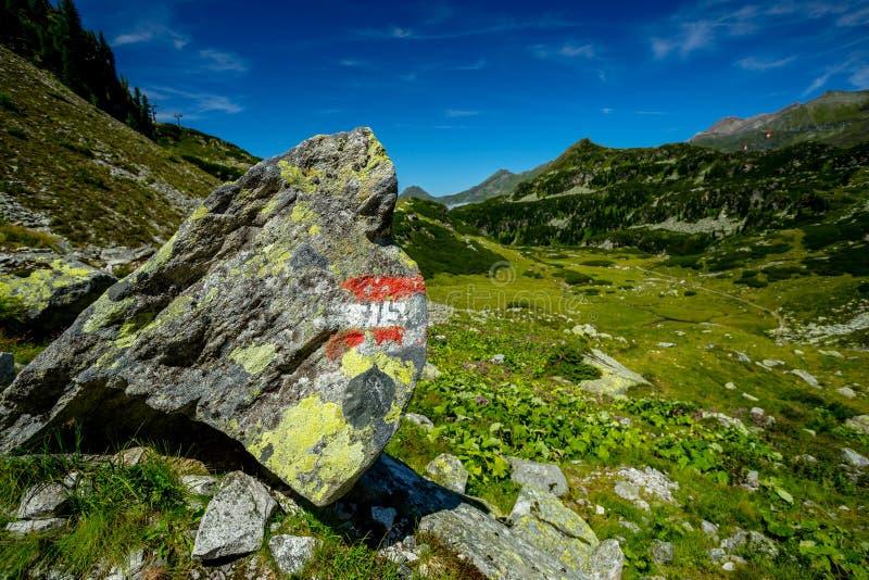 Sikten från den Rocky Alpine Trail Towards Lake Grà ¼nseen med stort vaggar med det turist- tecknet royaltyfri fotografi
