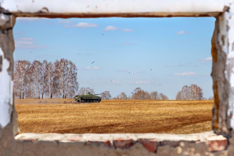 Sikten från det gamla förstörda fönstret av byggnad på grön behållare på larver rider in i ett fält av gult gräs under världskrig fotografering för bildbyråer