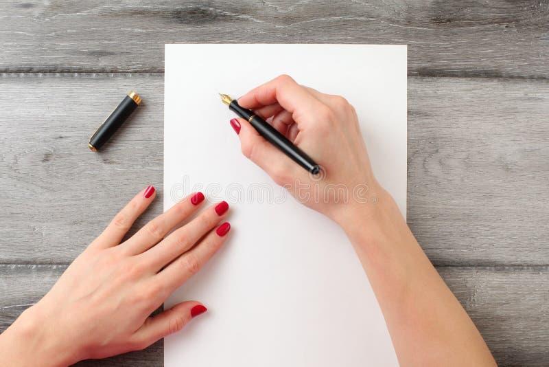 Sikten från ovannämnt till händer för kvinna` s med rött spikar och att rymma svart f arkivbilder