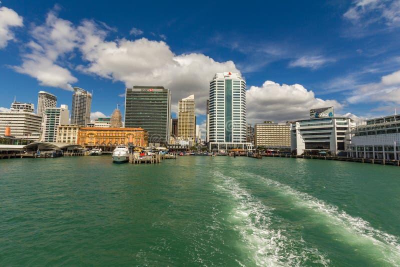 Sikten fr?n baksidan av en f?rja, som fartyget l?mnar den Auckland hamnen, med stadshorisonten i bakgrunden arkivbilder