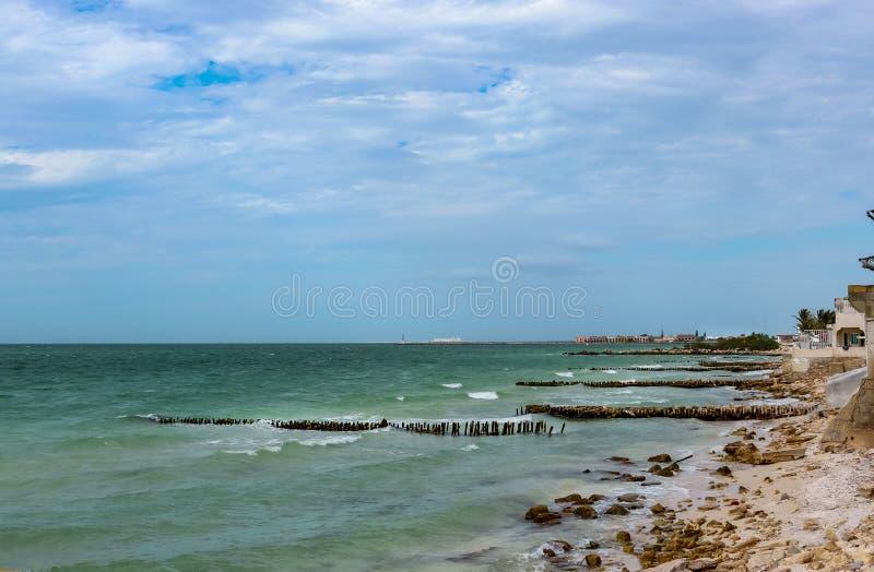 Sikten längs den eroderade stranden med sandfäktning i Progreso Mexico in mot den längsta pir för världar, som låter skepp anslut royaltyfri foto