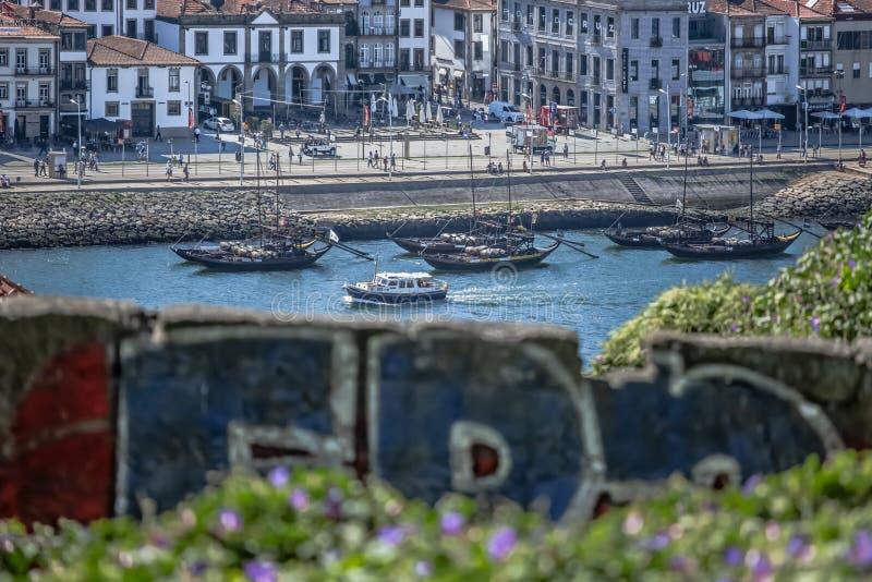 Sikten på den Douro floden med rabelofartyg och den Gaia staden som bakgrund, gör suddig stads- grafittikonstverk på det första p royaltyfri foto
