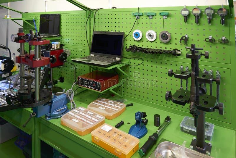 Sikten på grön arbetsplats med utrustning och hjälpmedel för delar för billastbildelar specificerar diagnostiskt beträffande kali arkivfoto
