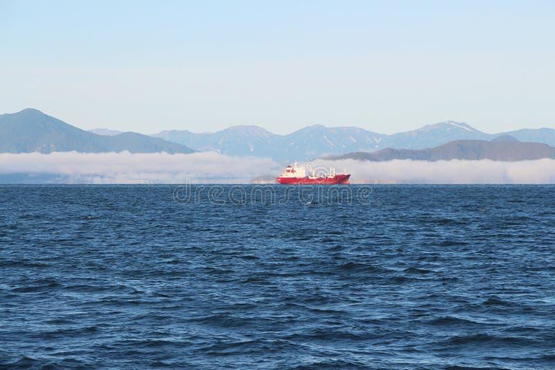 Sikten på lastfartyget kallade också fraktbåten i vattnet av den Avacha fjärden på den Kamchatka halvön, Ryssland arkivbild