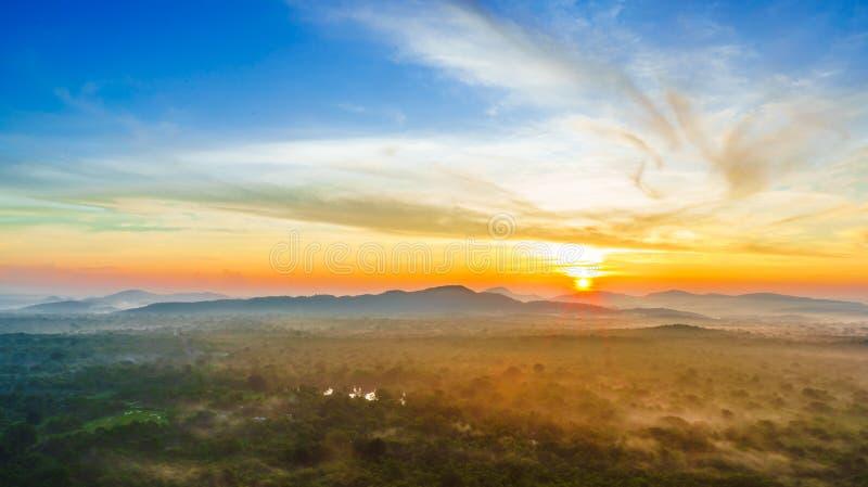 Sikten på soluppgång över den dimmiga djungeln från Pidurangala vaggar i Sri Lanka royaltyfri fotografi