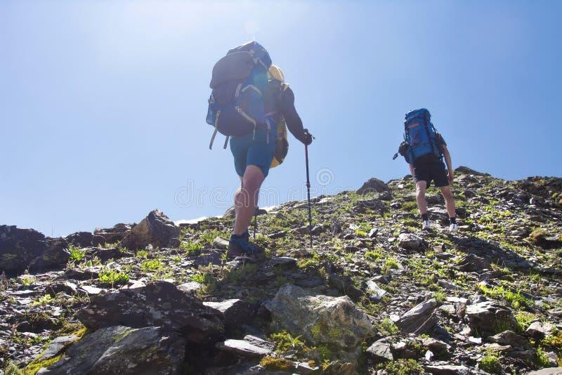 Sikten på två klättrare fotvandrar monteringen till maximumet av berget Fritidsaktivitet i berg Fotvandra sporten i Svaneti, Geor royaltyfri bild