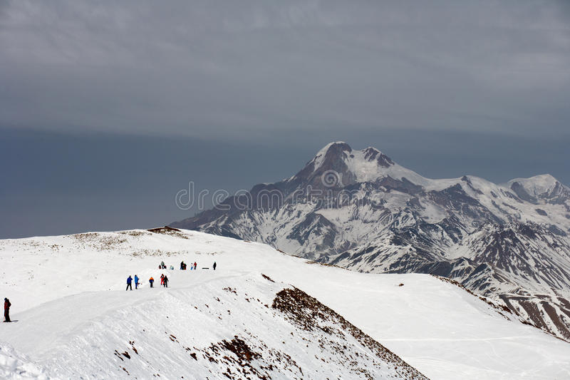 Sikten skidar på lutningen och härliga berg i afton Skidar semesterorten Gudauri, Kaukasus berg, Georgia royaltyfri foto