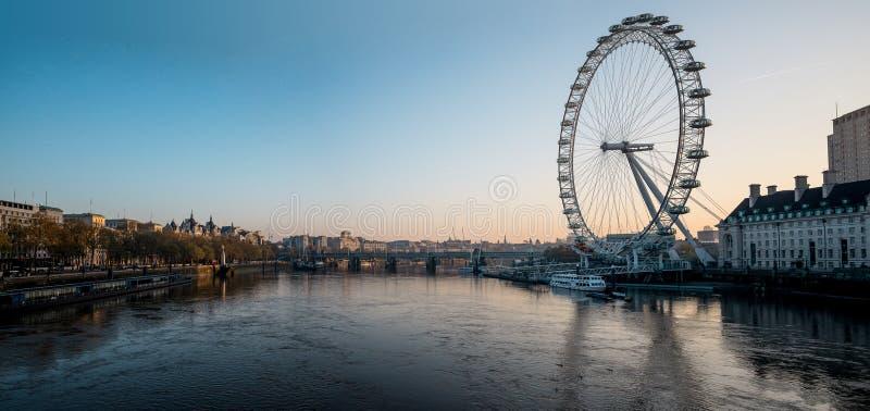 Sikten till det London ögat och Thames River från Westminster överbryggar tidigt på morgonen arkivfoto