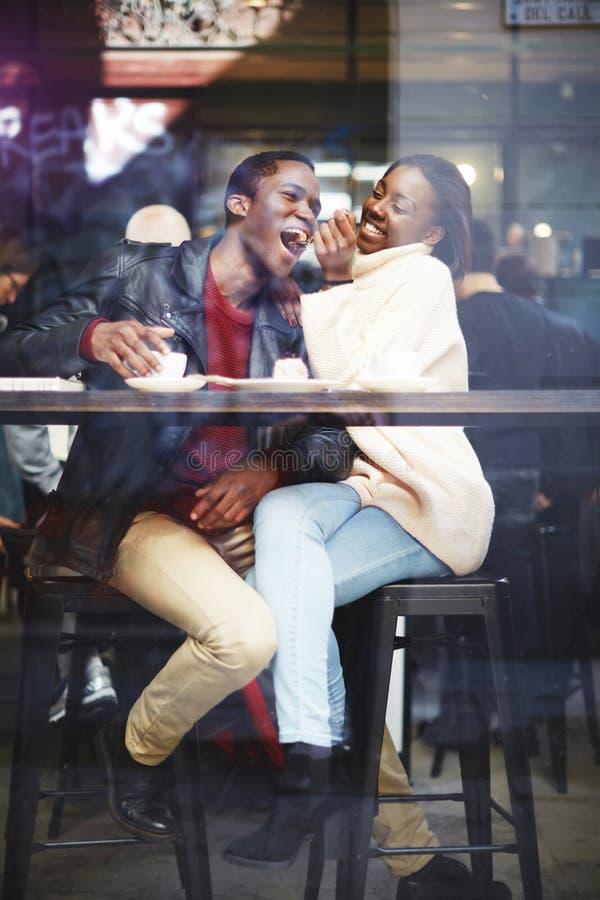 Sikten till och med kaféfönster av ett ungt lyckligt mörker flådde mannen och kvinnan som har gyckel, medan sitta tillsammans i s royaltyfria foton