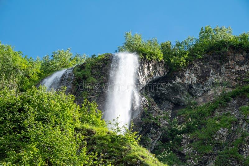 Sikter av de gr?na bergen med den h?gsta vattenfallet Klar bl?ttsky royaltyfri bild