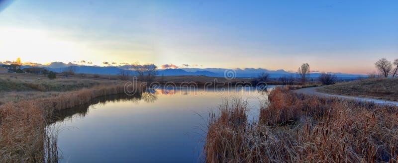 Sikter av den gå banan för Josh's damm, den reflekterande solnedgången i Broomfield Colorado som omges av Cattails, slättar och royaltyfri fotografi