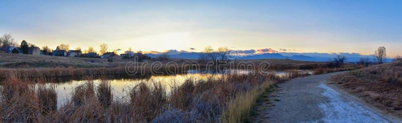 Sikter av den gå banan för Josh's damm, den reflekterande solnedgången i Broomfield Colorado som omges av Cattails, slättar och royaltyfria bilder