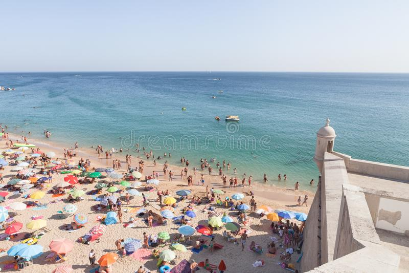 Sikter av den Sesimbra stranden och fästningen under blå himmel arkivbild