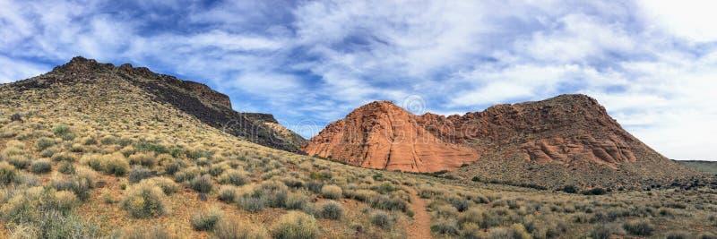 Sikter av sandsten och lava vaggar berg och ökenväxter runt om den nationella naturvårdsområdet för röda klippor på de gula runda royaltyfri foto