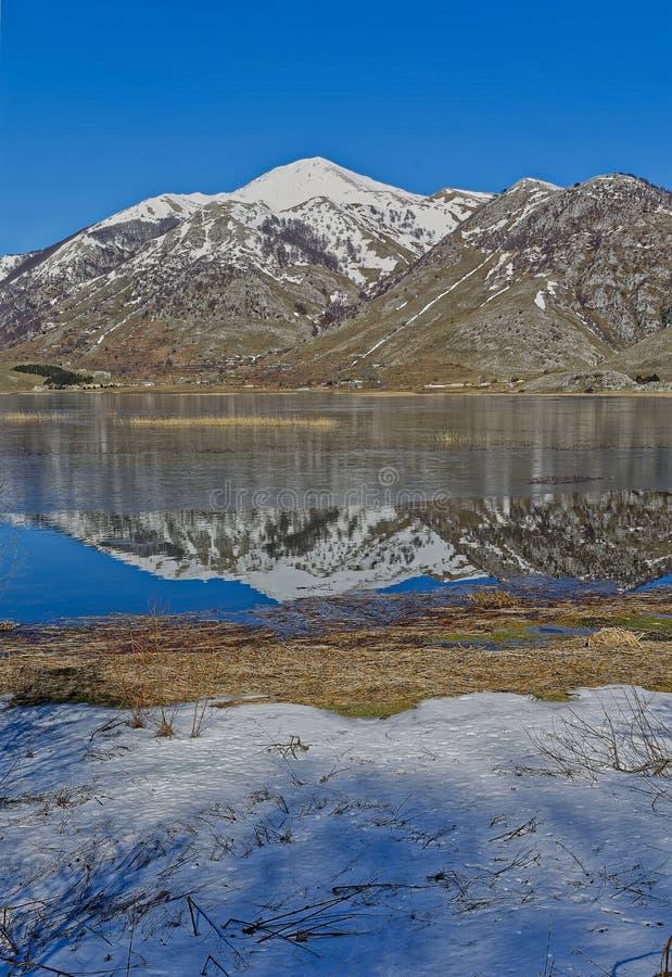 Sikter av sjön som är matese i vinter med nästan isgatan och dekorkade bergen Regionalt område av ‹för †massiven av arkivfoto