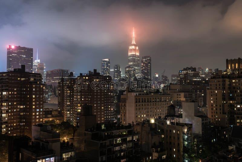 Sikter för byggnad för väldetillstånd dimmiga på nattetid arkivbild