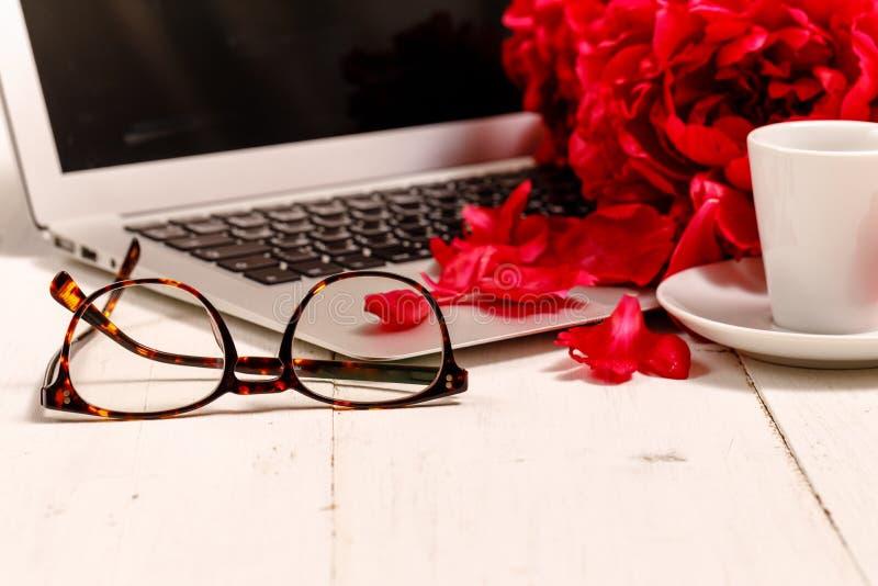 Siktskvinnors skrivbord för kontor med blommor Kvinnlig workspace med bärbara datorn, blommapioner, tillbehör, anteckningsbok, ex royaltyfri foto