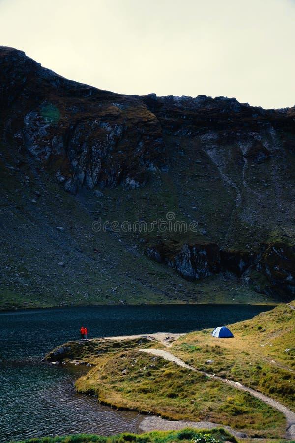 Siktspar av turister står adove sjön turism och tält för affärsföretag campa landskap nära vatten som är utomhus- på Lacul Balea royaltyfria foton