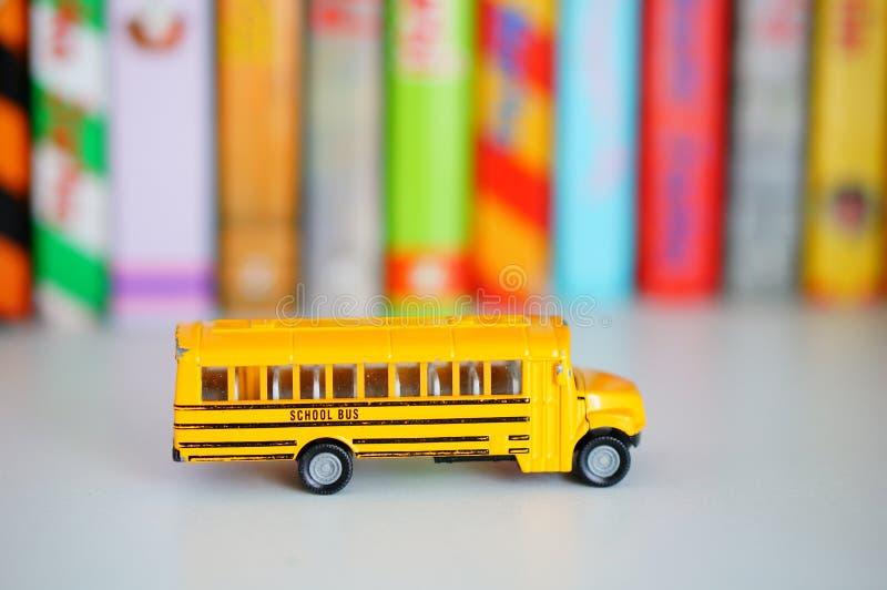 Siku toy school bus. POZNAN, POLAND - Mar 12, 2020: Yellow Siku toy school bus on a wooden shelf with books in soft focus background royalty free stock photos
