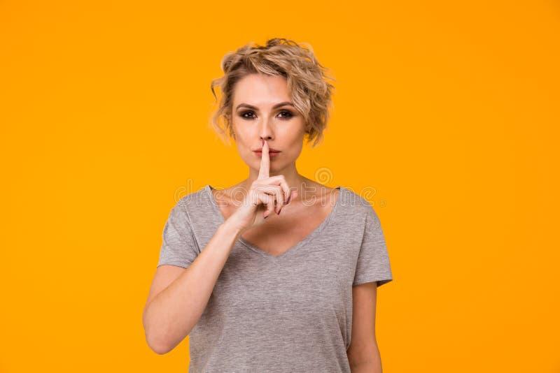 Silêncio A mulher que pedem o silêncio ou o secretismo com o dedo nos bordos acalentam a parede amarela do fundo do gesto de mão  imagens de stock