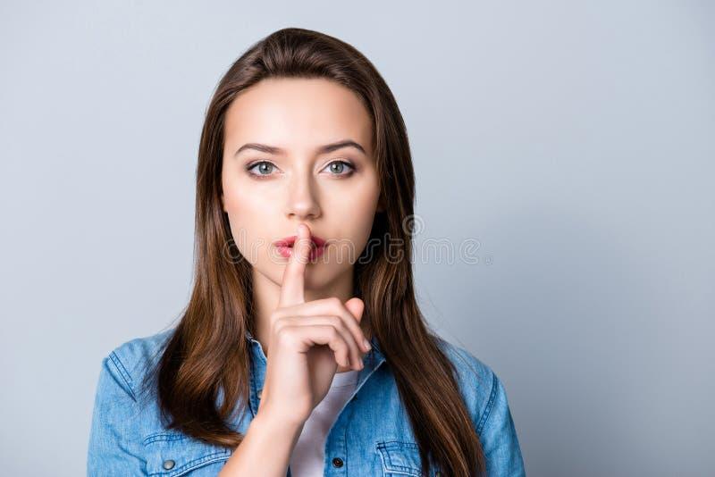 Silêncio, por favor! Feche acima do retrato da jovem mulher que guarda seu f foto de stock