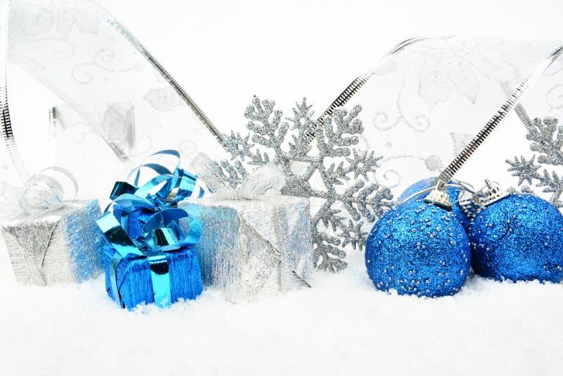Silber, blauer Weihnachtsflitter, Geschenke, Schneeflocke mit silbernem Band auf Schnee stockfoto