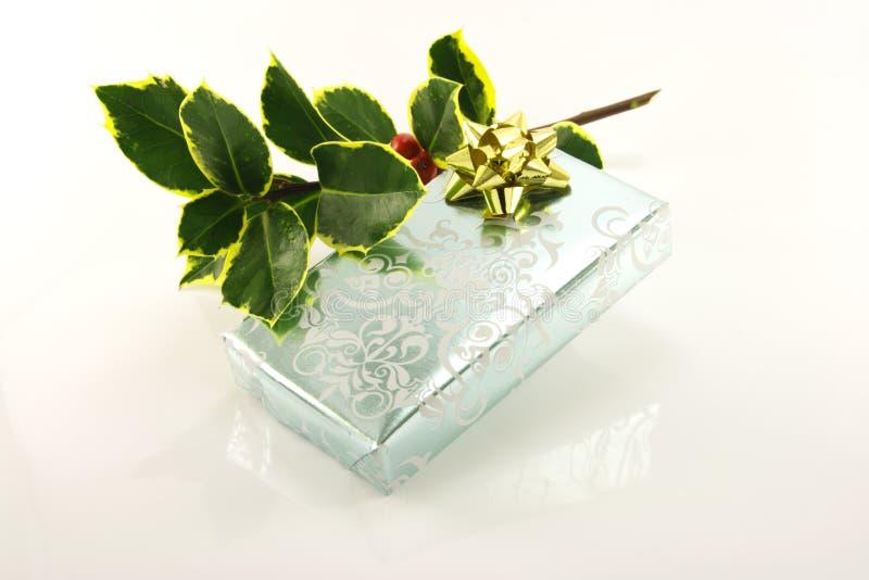 Silber eingewickeltes Geschenk und Stechpalme stockfotografie