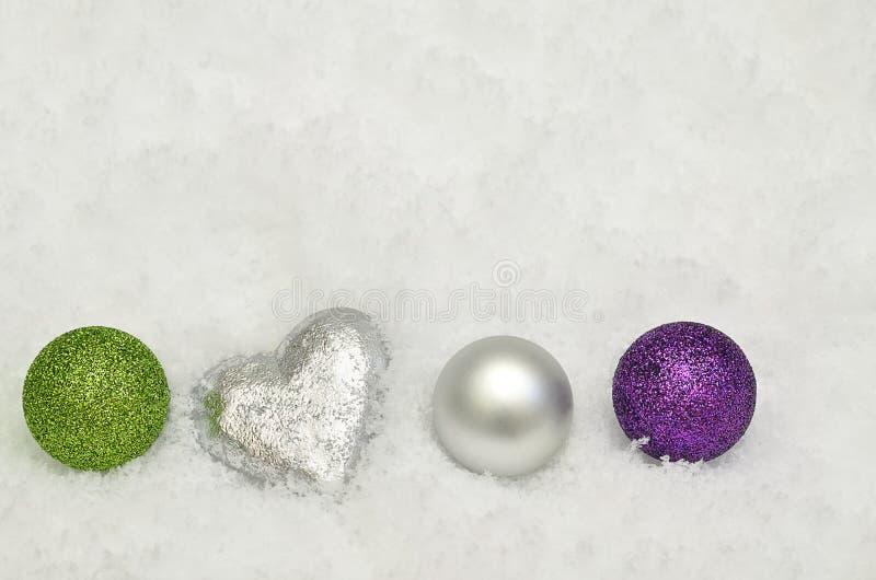 Silber-, Grüne und PurpurroteWeihnachtsbaumdekorationen auf Schneehintergrund stockfotos