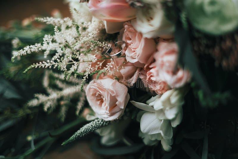 Silberhochzeitringe auf dem Bündel des Hochzeitsblumenstraußes gestaltungsarbeit Nahaufnahme lizenzfreie stockfotografie