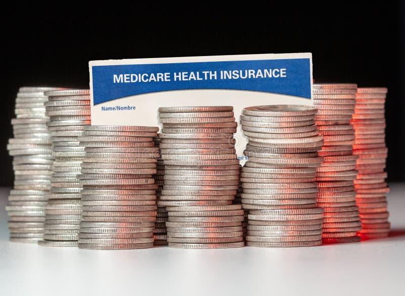 Silbermünzen mit Krankenversicherungskarte zur Veranschaulichung von Finanzierungsschwierigkeiten stockbild