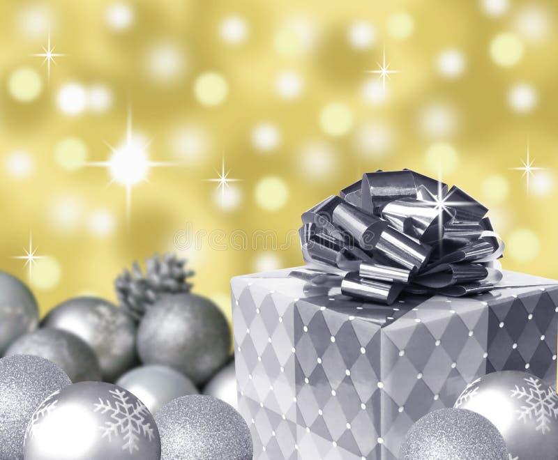 Silberne anwesende Bogen- und Weihnachtsbälle mit Schneeflocken und Goldabstraktem bokeh Hintergrund lizenzfreies stockbild
