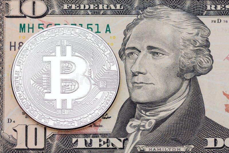 Silberne bitcoin Münze auf zehn Dollar Banknotenabschluß oben stockfoto