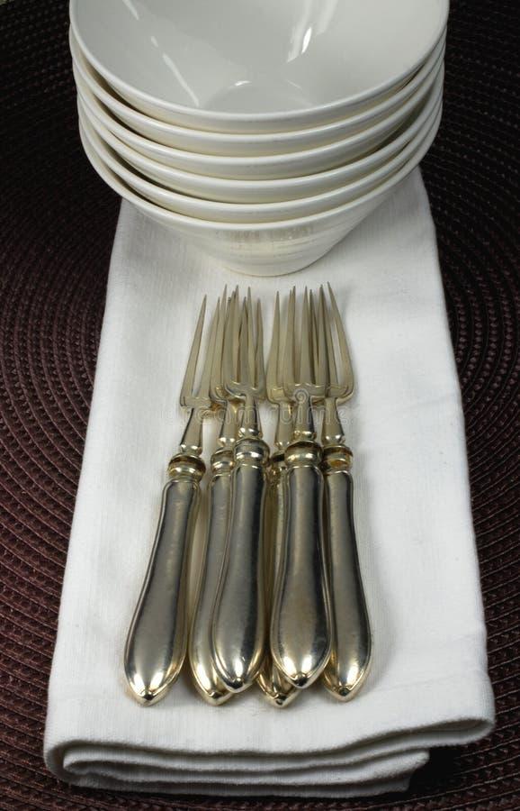Silberne Gabeln, porcelaine Schüsseln und Servietten stockfotografie