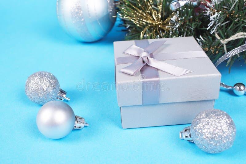Silberne Geschenkbox mit nettem seidigem Bogen und glänzender Weihnachtsflitter nahe Kieferniederlassung Neues Jahr und lizenzfreies stockbild
