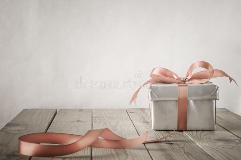 Silberne Geschenkbox und Bogen mit Weinlese-Effekt lizenzfreie stockfotos