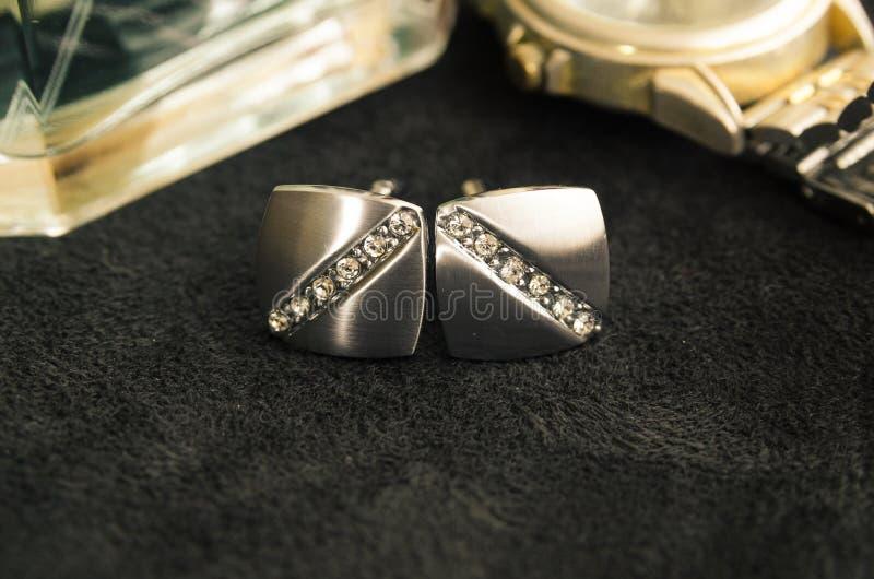 Silberne Manschettenknöpfe und Golduhr lizenzfreies stockbild
