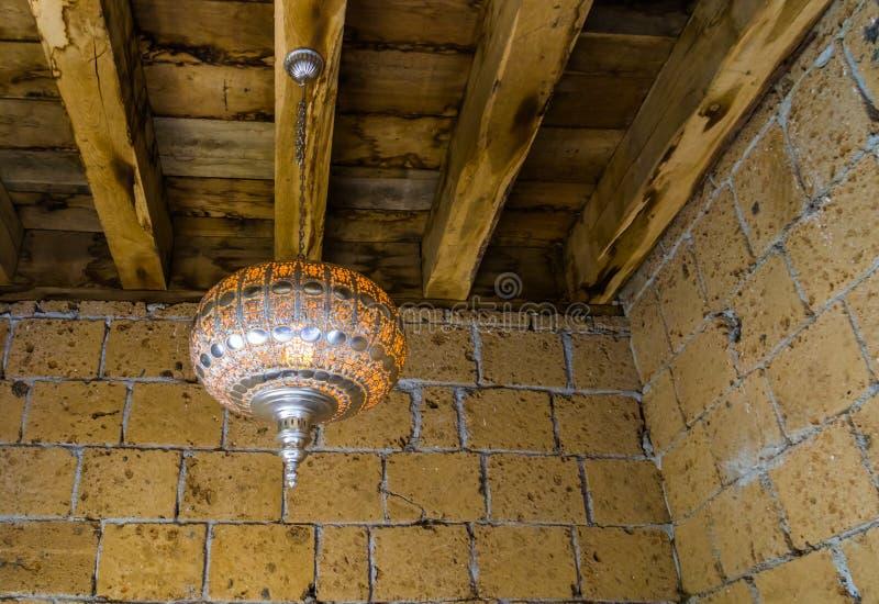 Silberne marokkanische beleuchtete Laterne, die an einem hölzernen Dach, an einem traditionellen Hauptinnenraum und an Dekoration stockfotografie