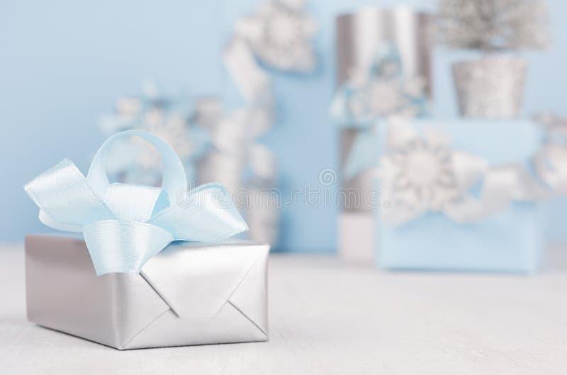 Silberne metallische Geschenkbox der Eleganz mit blauer Seidenbandnahaufnahme- und -weihnachtsdekoration auf weißem hölzernem Bre stockbild