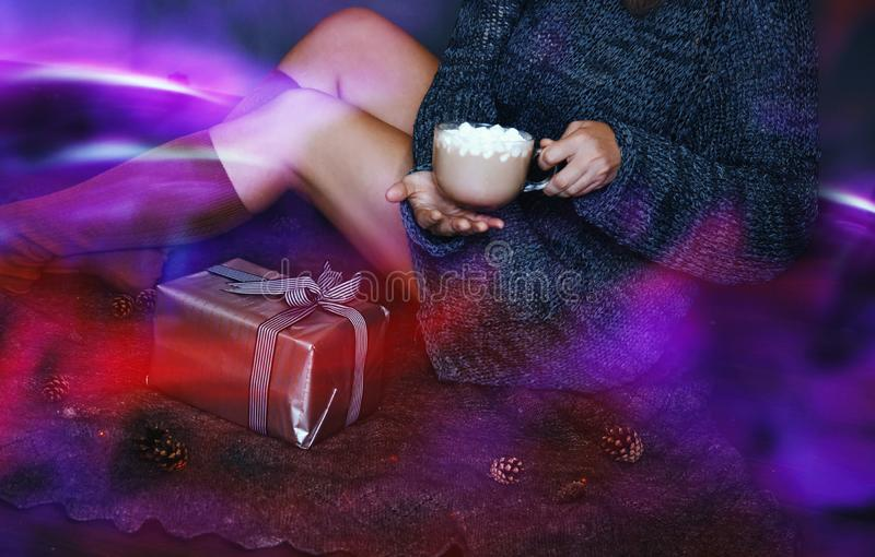 Silberne Neonfarbgeschenkbox mit Bogen und kleine Herzen in den Händen von Frauen auf dunklem Hintergrund Purpurrotes Neon stockfotografie