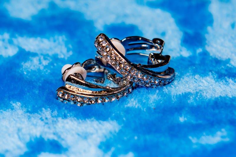 Silberne Ohrringe auf blauem Hintergrund stockbilder