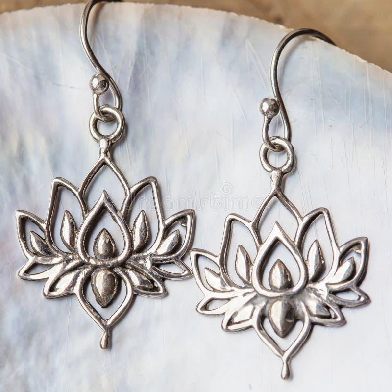 Silberne Ohrringe in Form des Lotos stockbilder