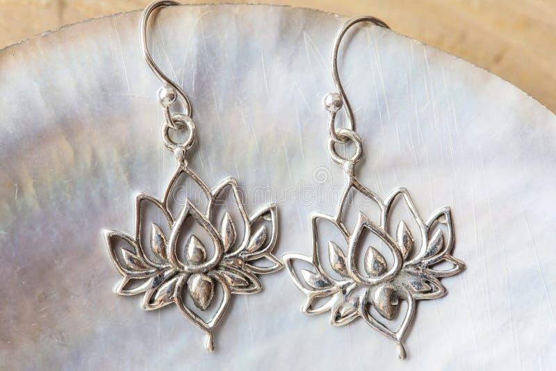 Silberne Ohrringe in Form des Lotos lizenzfreies stockfoto