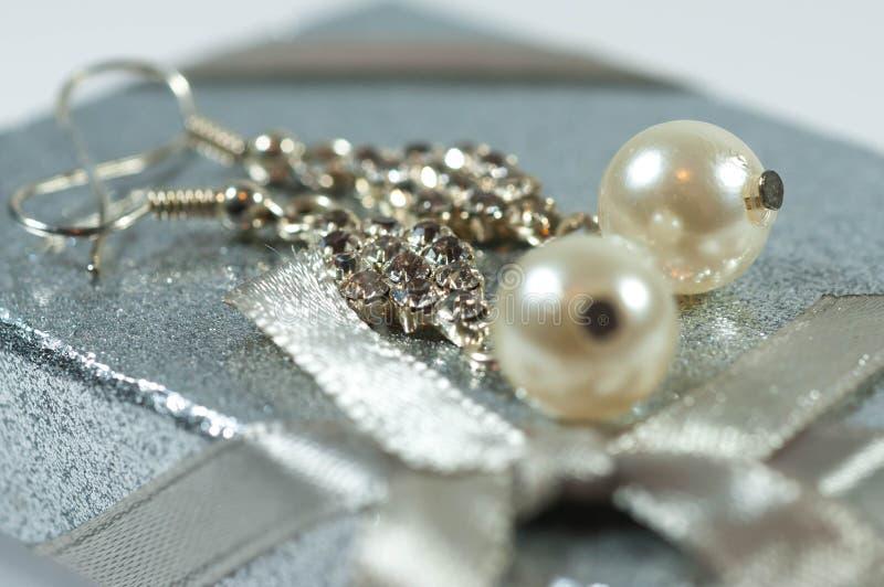 Silberne Ohrringe mit Edelsteinen und Perlen auf glänzender Geschenkbox lizenzfreies stockfoto