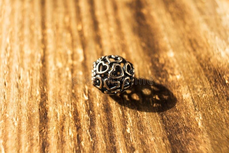 Silberne Perle für Armband auf hölzernem Hintergrund lizenzfreies stockfoto