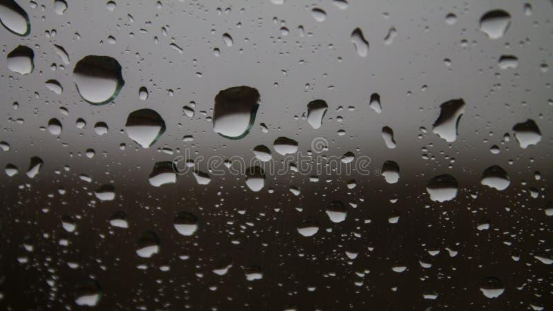 Silberne Regentropfen auf Glas, Nahaufnahme stockbild