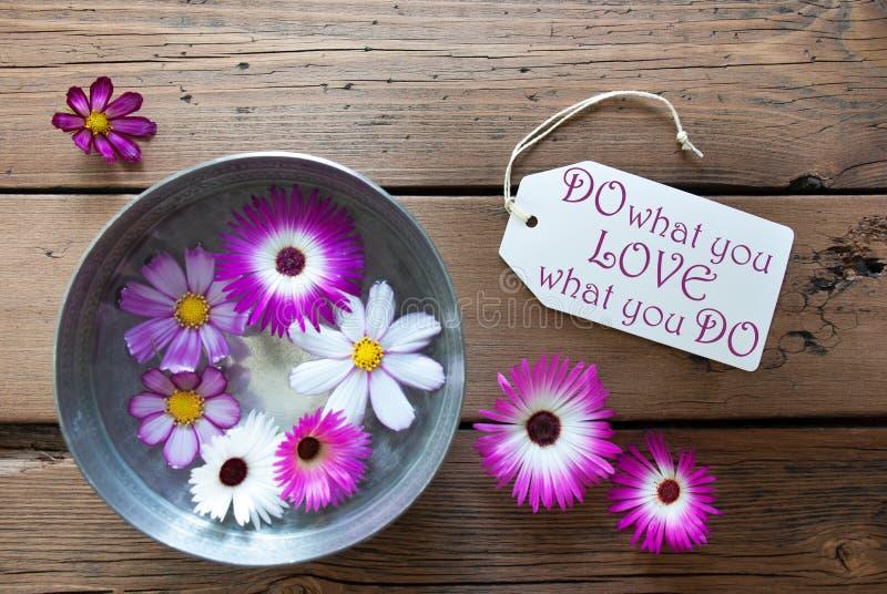 Silberne Schüssel mit Cosmea-Blüten mit Leben-Zitat tun, was Sie lieben, was Sie tun lizenzfreie stockfotos