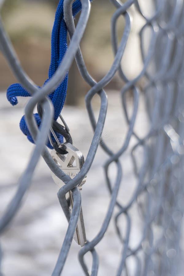 Silberne Schlüssel, die an einem Zaun hängen stockbilder