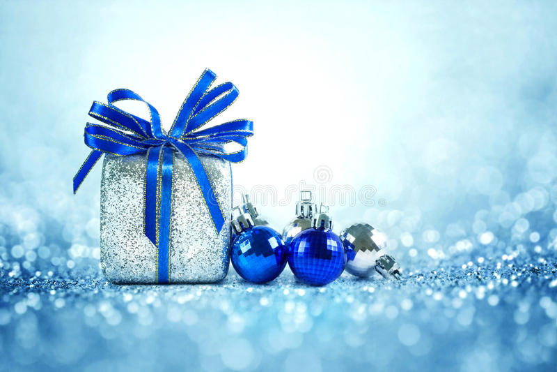 Silberne und blaue Weihnachtsbälle und -geschenke auf kühlem Funkeln lighti lizenzfreie stockbilder